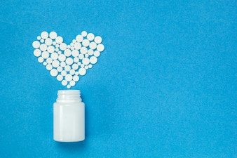 Pills in the form of a heart, a bottle. Tablets on a blue background.