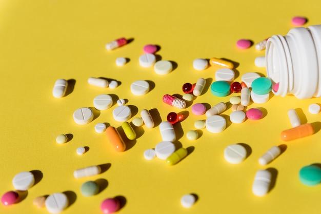 Пилюльки изолированные на желтой предпосылке таблетки и капсулы концепция здравоохранения и медицинских лекарств с крупным планом на пилюльках разливая от бутылки пилюльки рецепта. взгляд сверху.