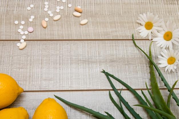 Таблетки, лимоны, ромашки и листья алоэ на деревянном фоне