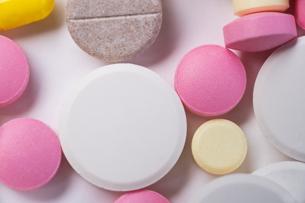 Pills of many shapes and colors grouped together.