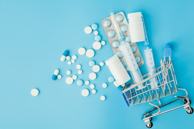Pills and medical injection in shopping trolley on blue background. creative idea for health care cost, drugstore, health insurance and pharmaceutical company business concept. copy space.