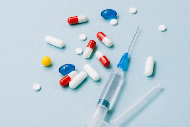 異なる色の丸薬とシリンジ