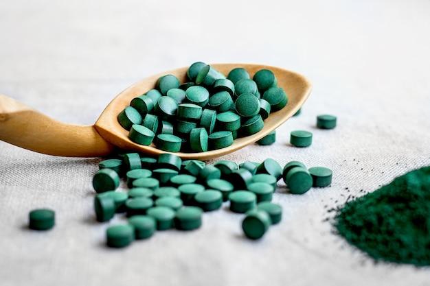 海藻スピルリナ、木のスプーンのクロレラの丸薬がクローズアップ。明るい背景に植物性タンパク質を含むベジタリアンスーパーフード