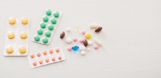 Таблетки на белом деревянном столе