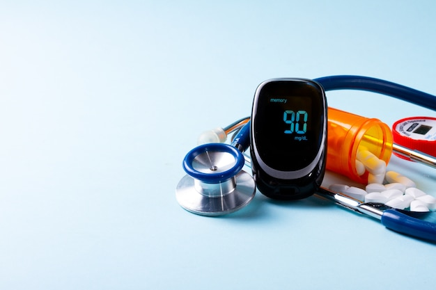 Pills in orange bottle with blood glucose meter and stethoscope on blue background