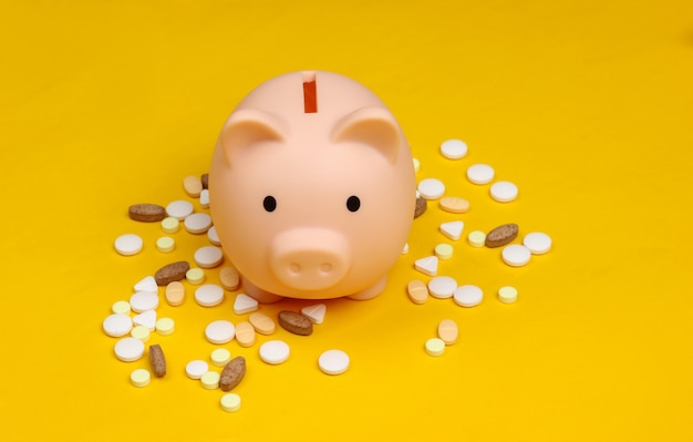 Pills and piggy bank on a yellow.