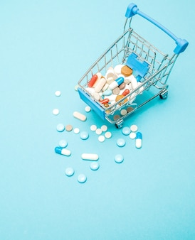 Pills and shopping trolley on blue background