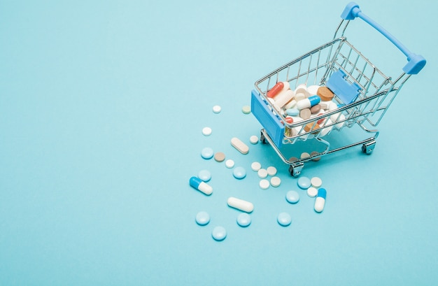 Pills and shopping trolley on blue.