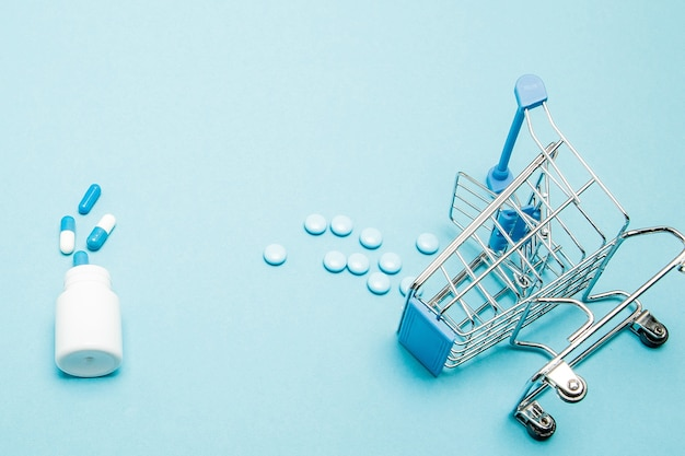 Pills and shopping trolley on blue