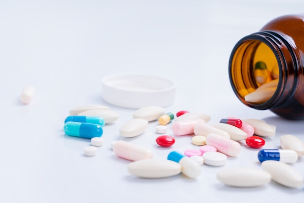 Pills spilling out of bottle on isolated white background