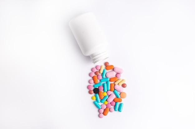 白い背景の上の白い容器からこぼれる錠剤。