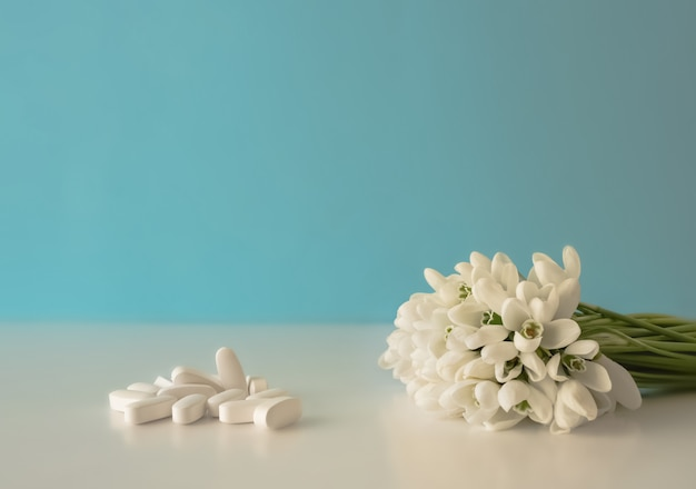 Pills spilling out of a pill bottle and flowers