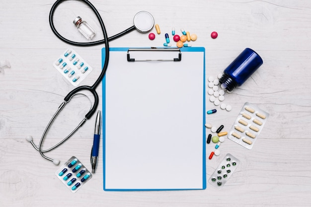 Pills and stethoscope around clipboard