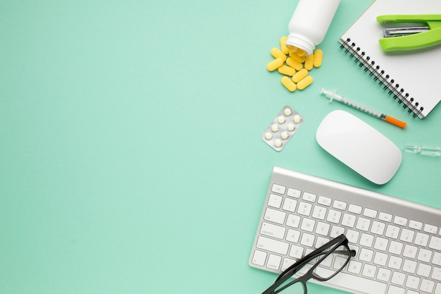 Pills and syringe with office accessories on green background