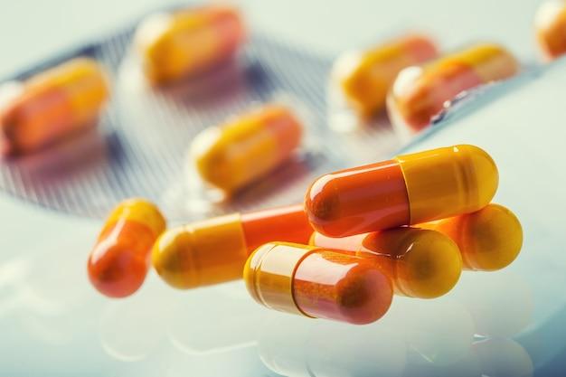 Таблетки таблетки капсулы или лекарство свободно лежат на стеклянном фоне.