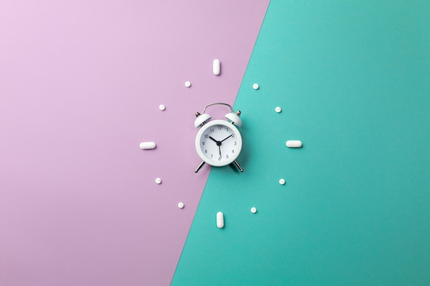 Pills, tablets and white alarm clock on on green and purple