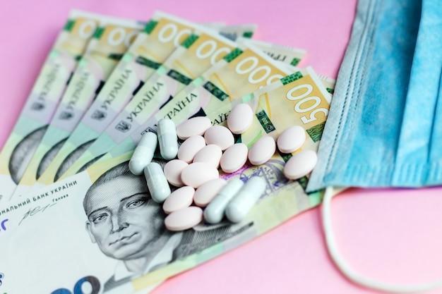 Таблетки, украинские деньги и защитная лечебная повязка. концепция здоровья.