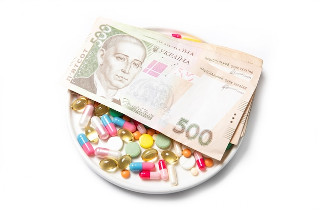 Pills and ukrainian money on a white. the concept of the rise in price of drugs.