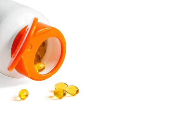 Pills of vitamin d3 and bottle with open cap