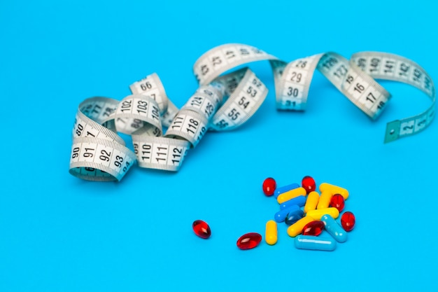 Pills for weight loss and tape measure on blue.