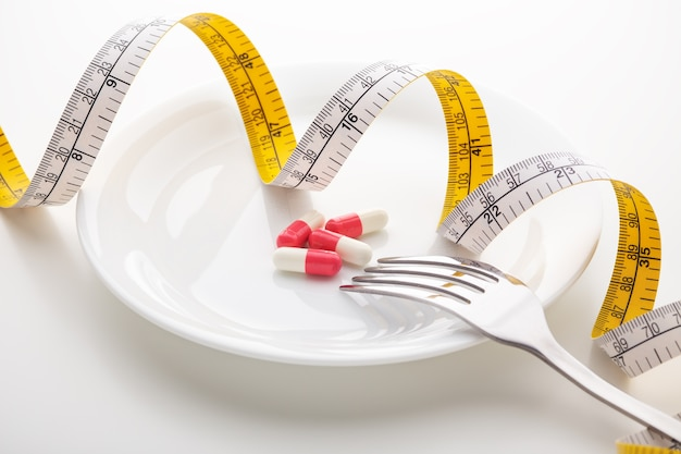 Pills on white plate with measuring tape