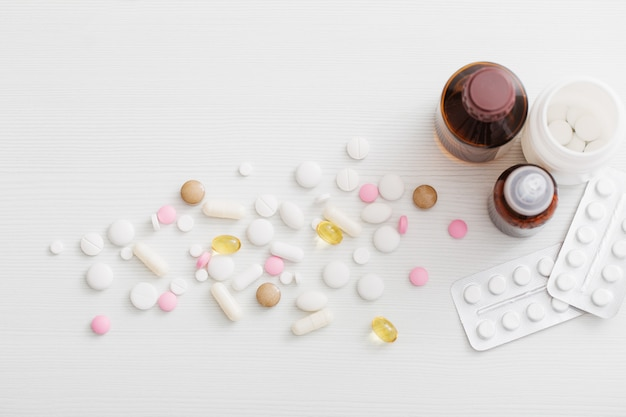 Pills on  white wooden table