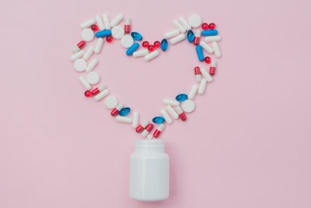 Pillole con contenitore su sfondo rosa