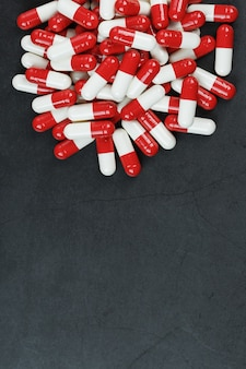 Pills with drugs are scattered on a black background
