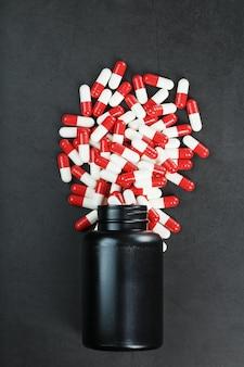 Таблетки с лекарствами рассыпаны из черной баночки на черном фоне.