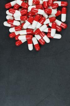Таблетки с наркотиками разбросаны на черном фоне