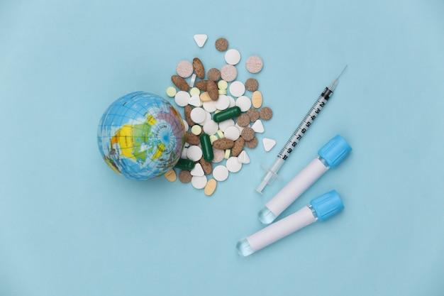 의료 테스트 튜브, 글로브, 파란색 배경에 주사기와 약. 치료. 코로나 19 감염병 세계적 유행. 평면도