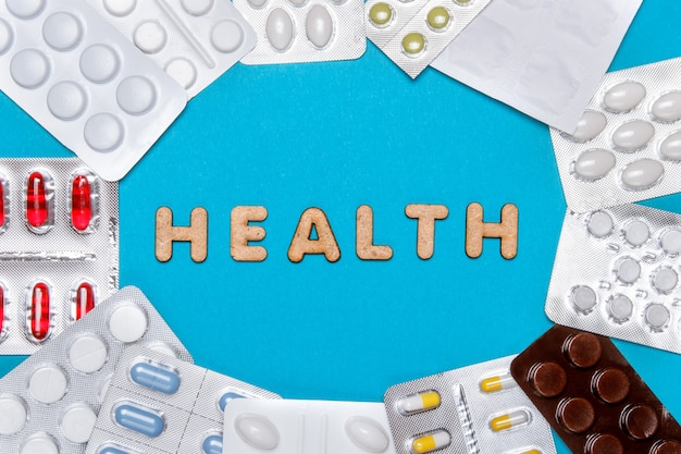Pills with wooden letters form the word health on a blue background. top view