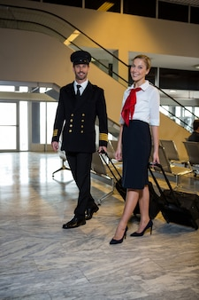 Pilot and air hostess walking with their trolley bags