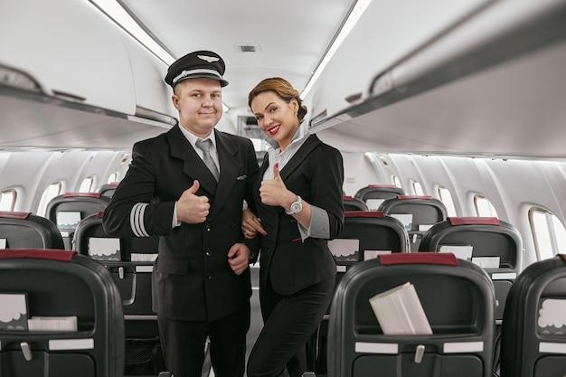 パイロットとスチュワーデスは、飛行機のジェット機の客室で親指を立てるジェスチャーを示します。モダンな飛行機のインテリア。笑顔のヨーロッパの男性と女性は制服を着ています。民間商用航空。空の旅のコンセプト