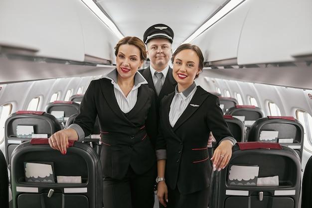 飛行機のジェット機の客室のパイロットとスチュワーデス。モダンな飛行機のインテリア。笑顔のヨーロッパの男性と女性は制服を着てカメラを見ています。民間商用航空。空の旅のコンセプト
