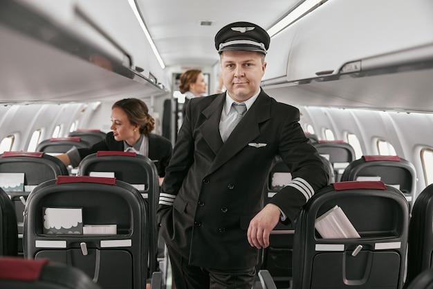 現代の飛行機のジェット機の客室のパイロットとスチュワーデス。女性は飛行機を飛ばす準備をします。飛行機チームはユニフォームを着ます。カメラを見ている男。民間商用航空。空の旅のコンセプト