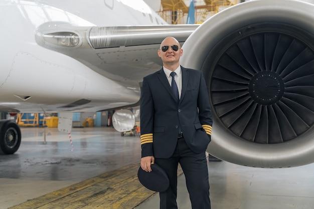 비행기의 터빈 날개 근처에서 포즈를 취하는 검은 양복의 조종사