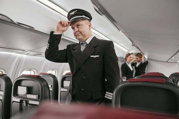 現代の飛行機ジェットの客室のパイロット。男の背景にスチュワーデスのぼかし。飛行機チームはユニフォームを着ます。民間商用航空。空の旅のコンセプト