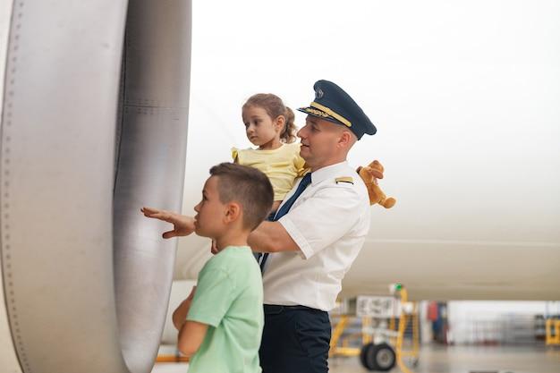 항공기 격납고에 소풍을 온 두 명의 어린 아이에게 비행기의 일부를 보여주는 제복을 입은 조종사. 항공기, 여행, 어린 시절 개념
