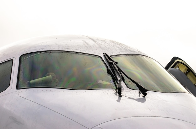 The pilot's cockpit aircraft with wipers on the windshield, rain drops of water in cloudy weather.