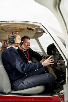 Pilot in training and flight instructor in the cockpit of an airplane