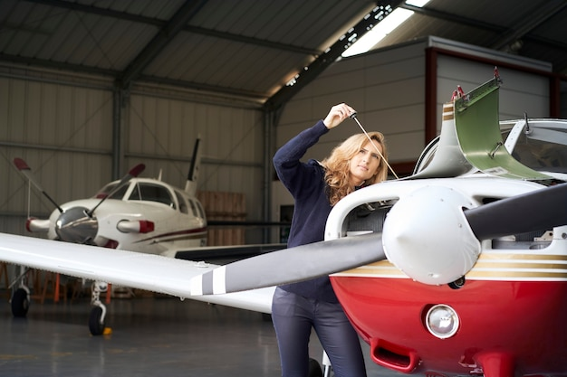 Pilot woman in the hangar doing the maintenance of the engine of a small plane
