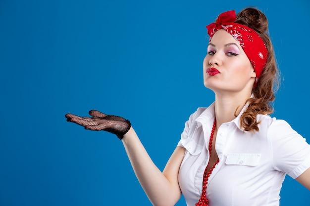 Пин-ап женский портрет. красивая ретро-женщина в белой рубашке с красными губами и старомодной прической с рукой, указывающей в сторону