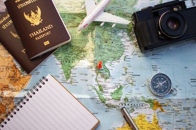 Pin on location map for travel plan with passport compass camera and notebook.