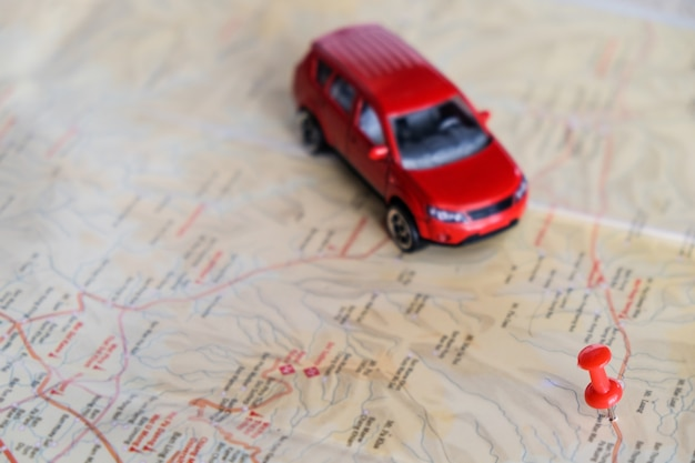 Pin on a map and car toy mark where to go.