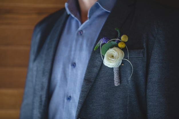 A pin of rose white rose and yellow blossoms in the jacket of a man.