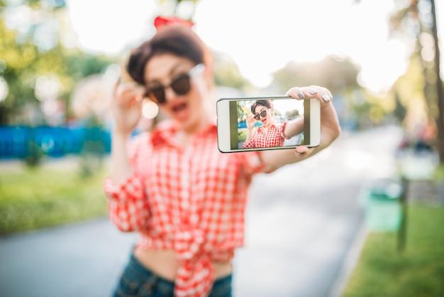サングラスの女の子、公園、ヴィンテージのアメリカンファッションで撮影したselfieをピンで留めます。ピンナップスタイルで魅力的な女性