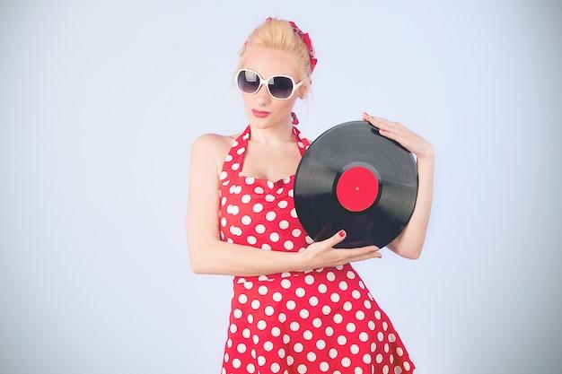 Очаровательная девушка в винтажном платье с виниловой пластинкой