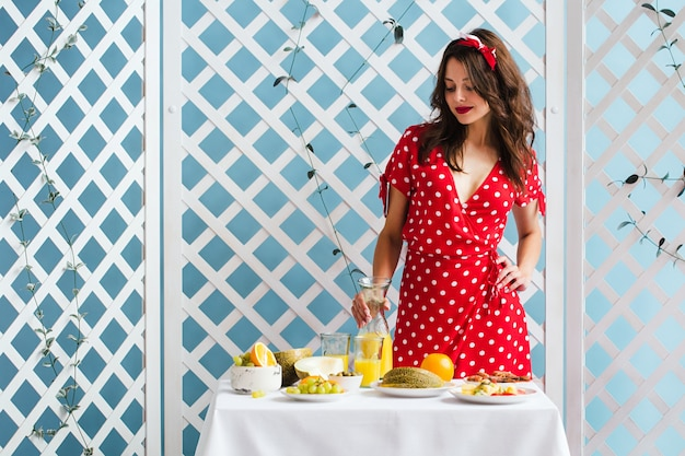 Pin-up girl in a red dress with a carafe of orange juice in her hands