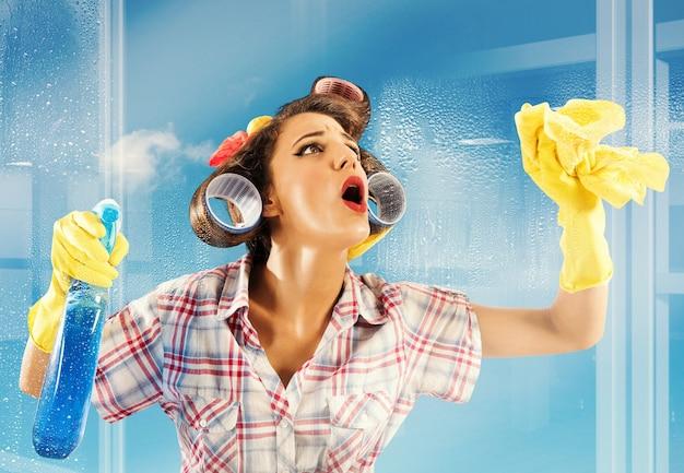 Очаровательная домохозяйка дышит на чистом стекле